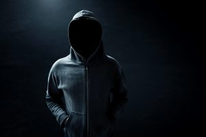 Hacker standing alone in dark room